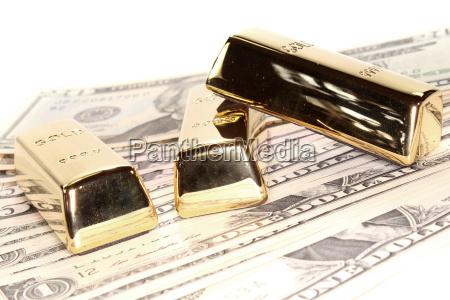three large gold bars on dollar