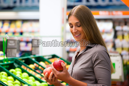 woman in supermarket buying fruit