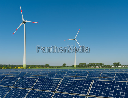 solar panels and wind turbines against