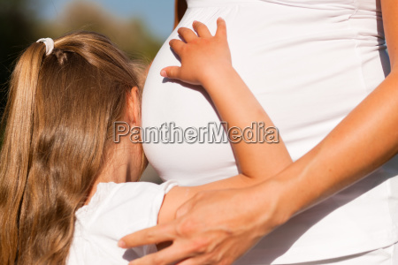 pregnancy girl touching pregnant mother