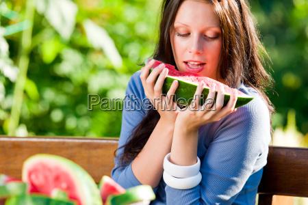 eating fresh melon beautiful young woman