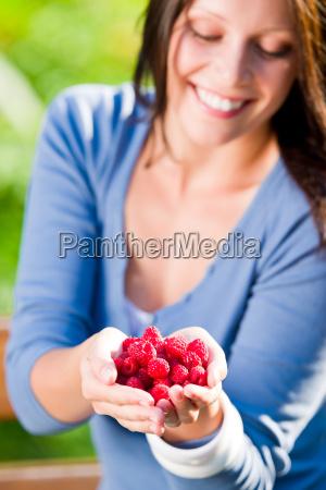 fresh raspberries hold hand cheerful smiling