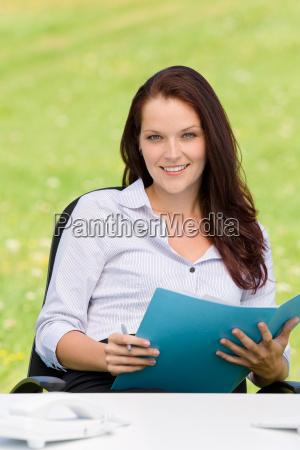 businesswoman in nature attractive smile folder