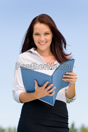 businesswoman in sunny nature smiling hold