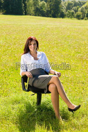 attractive businesswoman sit armchair sunny meadow