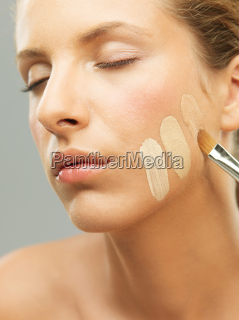 woman trying shades of foundation on