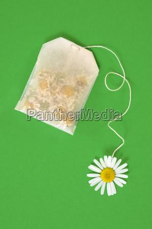 bag of chamomile tea over green