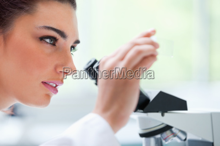 young woman looking at a microscope