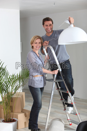 a couple installing a lamp in