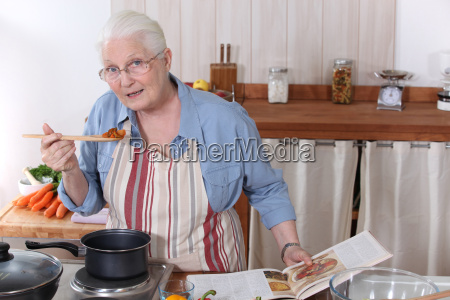 elderly woman cooking dinner with the