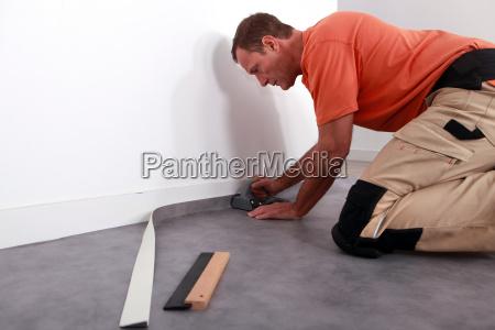 man putting down linoleum on a