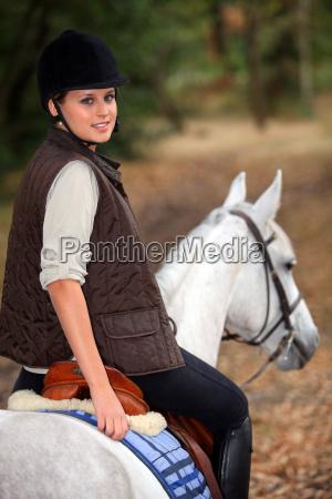 young woman riding a beautiful white