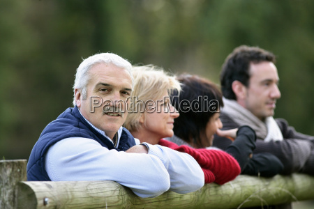 family leaning against fence