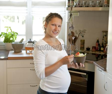mujer joven embarazada con ensalada