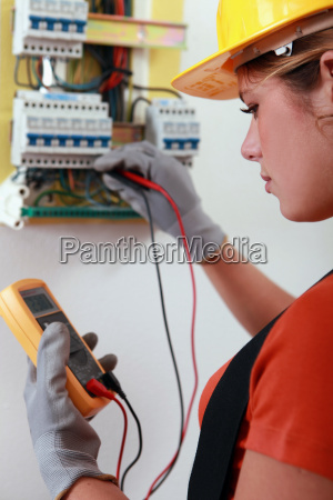 female electrician checking the wiring on
