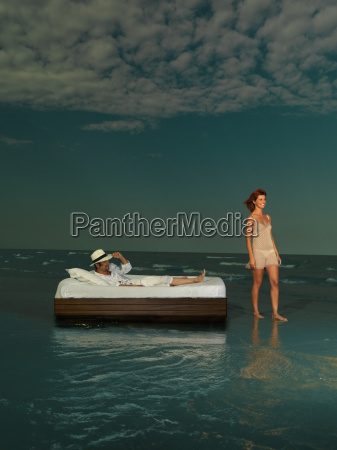 young couple laying bed surrounded by