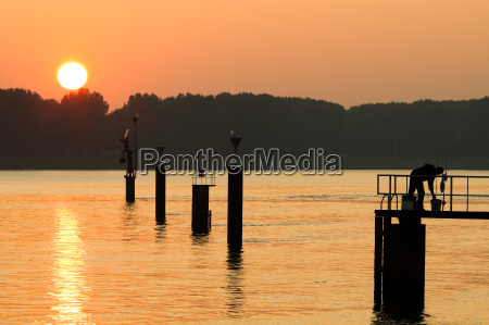 sunset at the riverside with fisherman