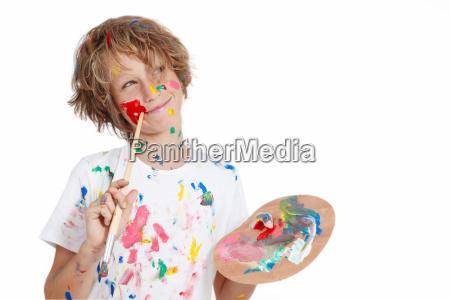 child with paint brush planning mischief