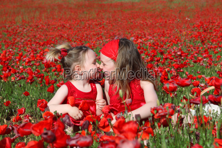 little girls sitting in summer poppy