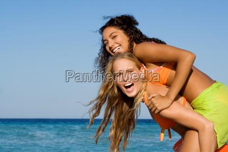 diversity mixed race friends playing piggyback