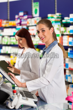 pharmacist with pharmacy assistant in pharmacy