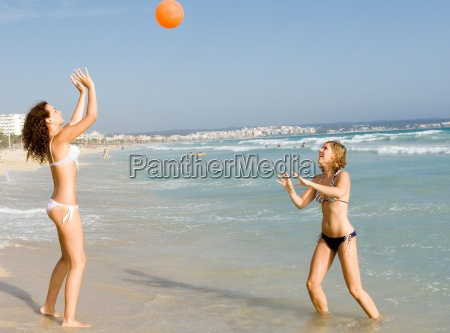 happy teens playing ball on beach