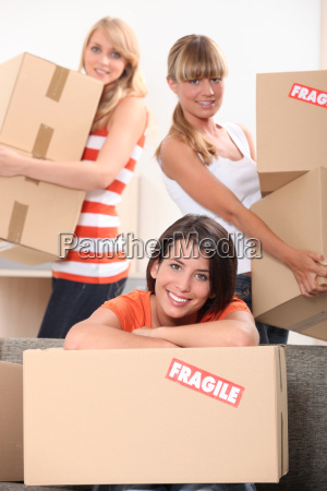 three young women moving cardboard packing