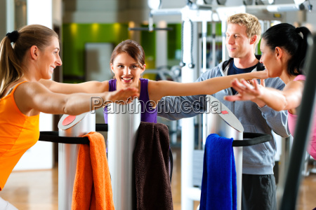 women and trainer in gym before