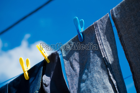 washed blue jeans drying outside under