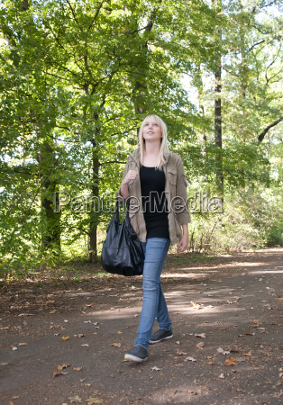 young woman walks in park
