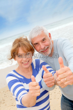 happy senior couple with thumbs up