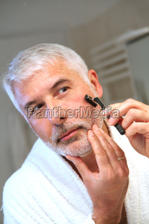 portrait of senior man shaving beard