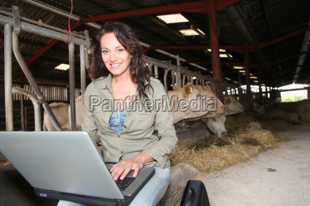 veterinarian in barn with laptop computer