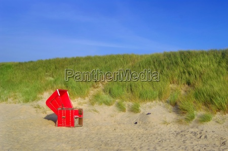 red beach chair in the dunes