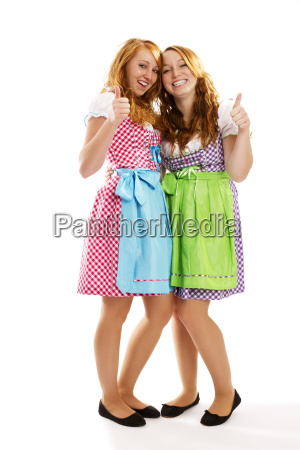 two women in dirndl show thumbs