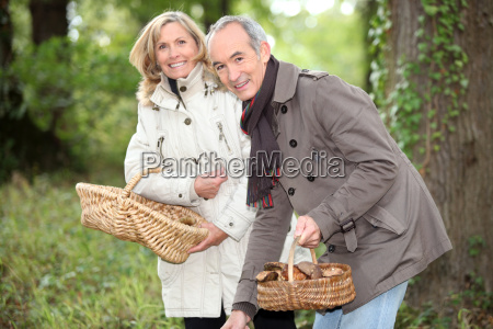 senior couple gathering mushrooms