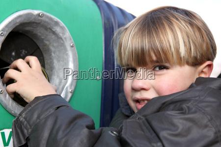 little boy throwing a glass bottle