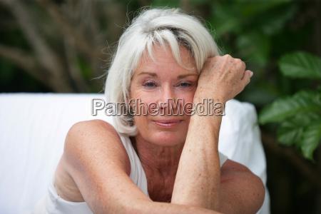 grey haired woman sat in garden