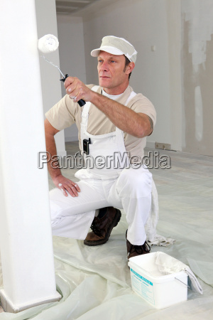 decorator using roller to paint wall