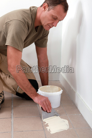 man spreading tile adhesive on old