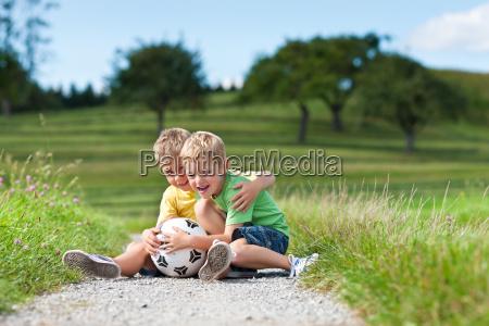 duas criancas com o futebol sentado
