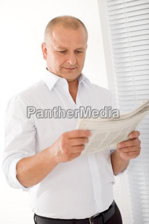 senior businessman happy read newspapers portrait