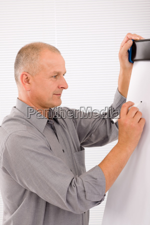 mature businessman writing at empty flip