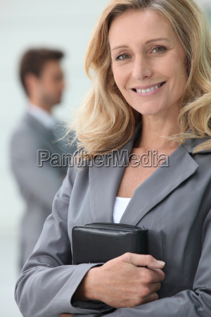 smiling businesswoman holding personal organiser with