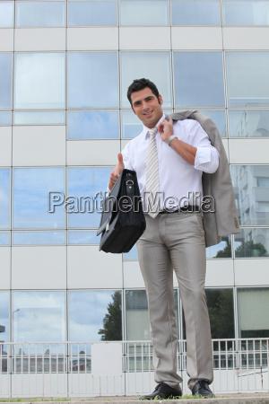 businessman outside glass building holding satchel