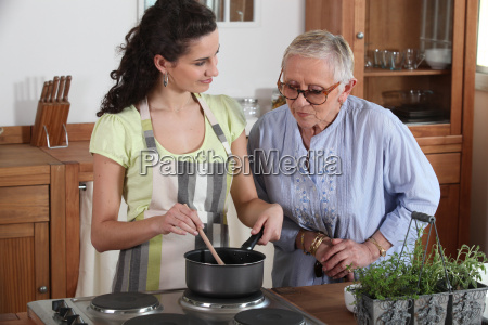 young woman cooking for an elderly