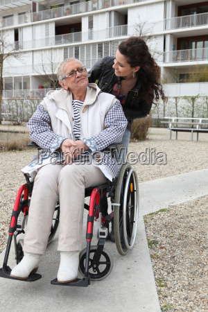 young woman pushing an elderly woman