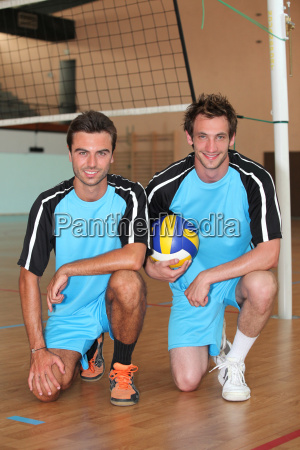 team mates kneeling with volley ball