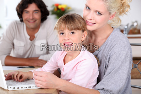 parents and daughter using a laptop