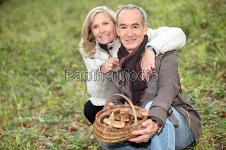 senior couple collecting mushrooms in the
